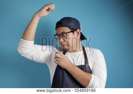 Portrait Of Funny Young Male Asian Chef Or Waiter Smelling His Own Body, Bad Body Odor Problem, Agai