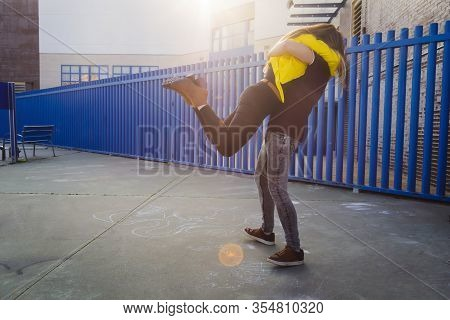 Young Woman Wearing A Yellow Jacket Leaps On His Boyfriend, Tenderness Moments Of Love