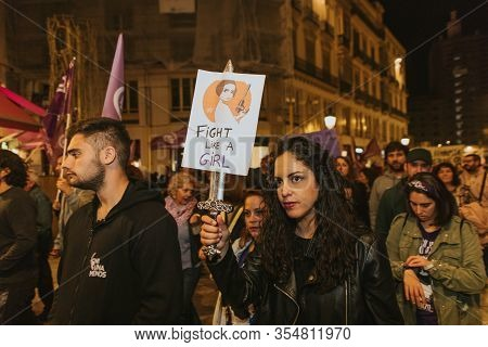 Malaga, Spain - March 8th, 2020: Young Woman Showing Feminist Banners And Protest Placards During Fe