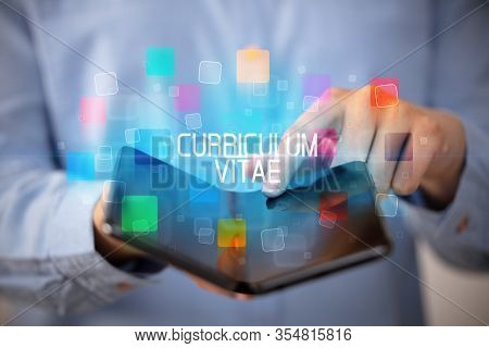 Young man holding a foldable smartphone with CURRICULUM VITAE inscription, educational concept