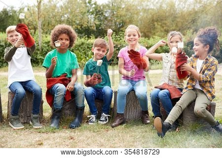 Portrait Of Children On Outdoor Activity Camping Trip Eating Marshmallows Around Camp Fire Together