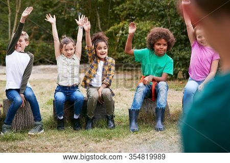 Children On Outdoor Activity Camping Trip Sit Around Camp Fire With Arms Raised Answering Question