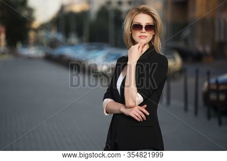 Young fashion blond business woman walking on city street  Stylish female model in black blazer and sunglasses