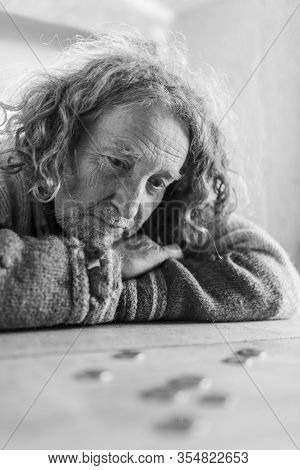 Black And White Image Of Worried Senior Man Leaning His Head On His Arms, Sadly Looking At This Last