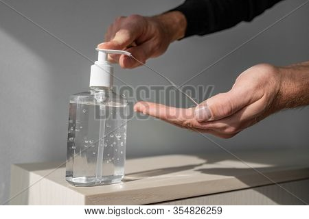 Hand sanitizer alcohol gel rub clean hands hygiene prevention of coronavirus virus outbreak. Man using bottle of antibacterial sanitiser soap.