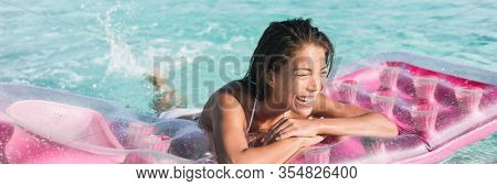 Swimming pool fun beach summer vacation woman relaxing on float toy sunbathing relax on pink air mattress inflatable floating on blue ocean background panoramic banner.