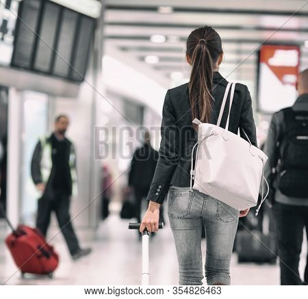 Travel background airport terminal passengers walking in lounge. Asian woman walking from behind with purse carrying luggages for delayed flights to vacation holidays.
