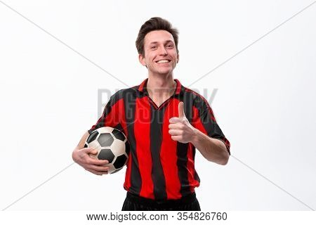 Excited Soccer Player In A Red Sportswear Showing Thumb Up Holding Soccer Ball. Enjoy Training For S