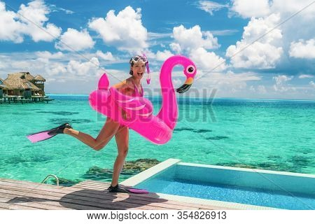 Happy fun beach vacation woman tourist ready to take the plunge jumping in luxury swimming pool at Tahiti resort hotel with snorkel fins and pink flamingo pool float. Funny girl running on holidays.