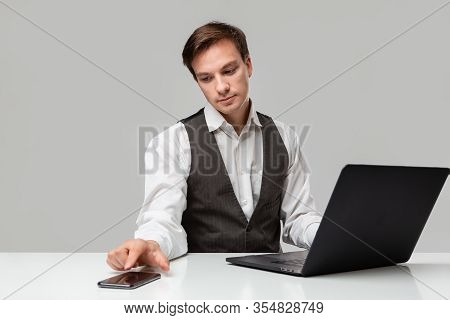Businessman In A White T-shirt And Grey Vest Working On A Laptop. Man Looking At The Camera. Daily B