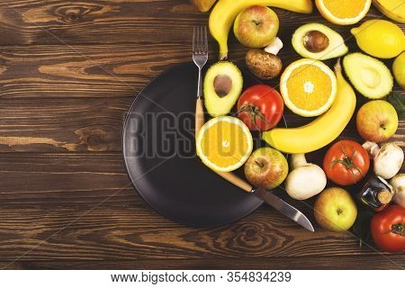 Intermittent Fasting Concept. Black Plate On A Wooden Table With Food, Located At The Time Of The Pe