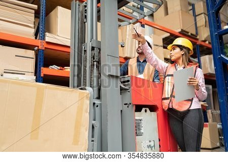 Low Angle View Of Confident Supervisor Pointing To Employee Operating Forklift By Rack At Warehouse