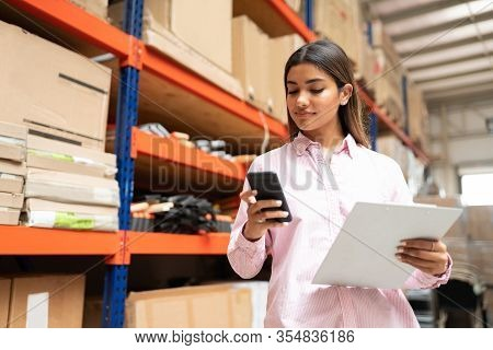 Young Latin Warehouse Worker Using Smartphone While Holding Merchandise List Against Rack At Factory