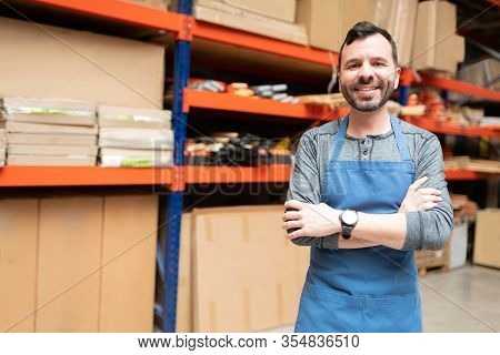 Smiling Handsome Salesman Standing With Arms Crossed While Making Eye Contact Against Rack At Hardwa