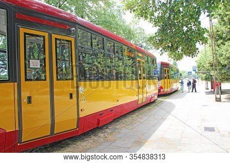 Lodz / Poland. 18 July 2019:  People Board Tram. Passengers Enter Tram. Blooming Linden. Urban Trans