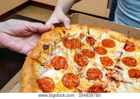 Hands Of Hungry People Taking Hot Delicious Italian Pepperoni Pizza, Home Delivery Concept.