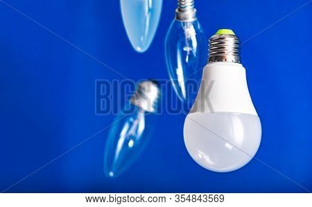 Different Bulbs Fall Down. Electric Lighting. Blurred Background. Power Saving Led Lamps In Comparis
