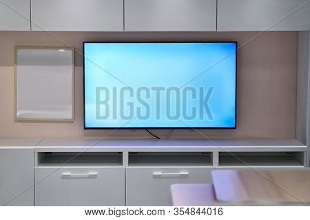 Tv room with bright interior and glowing blue light of LCD screen