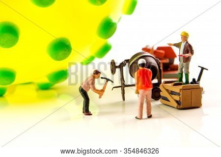 Closeup Of Big Corona Virus With A Team Of Miniature Figurines Of Workers Preparing For Taking Actio
