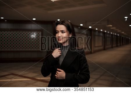 Dramatic Portrait Of A Beautiful Young Woman In A Black Coat In An Underground Passage.mosaics On Th