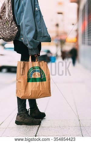 Girl With Backpack Doing Ecological Shopping With Paper Bag In Hand. Recycling Concept. Vertical Sto