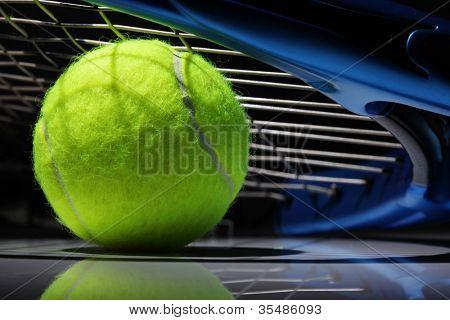 Tennis racquet resting on top of a tennis ball
