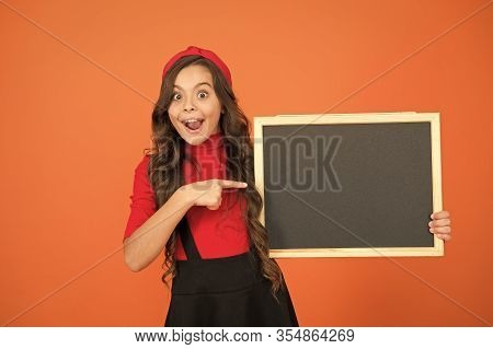 New Back To School Product. Happy Girl Point Finger At Blackboard. Little Child Presenting Product.