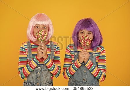 Sugary Food To Keep For Yourselves. Small Children Hold Lollipops Yellow Background. Little Girls En