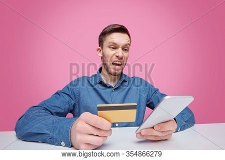 Angry guy with plastic card looking at screen of smartphone while expressing fury or irritation in isolation