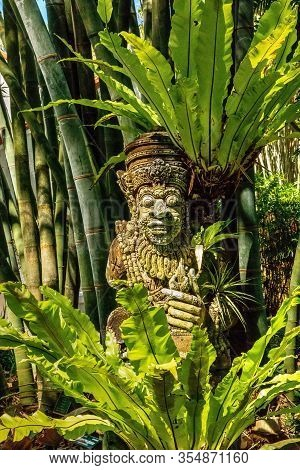 Statue Of Hindu Temple Guardian In A Tropical Garden.