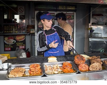 Subotica, Serbia - March 26, 2016: Woman, A Chef In A Rostilj Stand Flipping Beef Pattys (pljeskavic