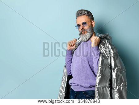 Gray-haired, Bearded, Aged Man In Purple Pullover And Sunglasses, Silver Colored Down Puffy Jacket,