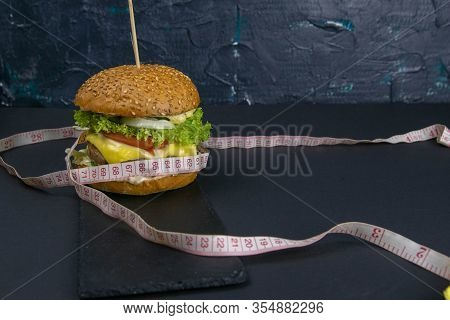 Hamburger For Weight Loss. The Concept Of Losing Weight. Juicy Hamburger Wrapped In Measuring Tape O