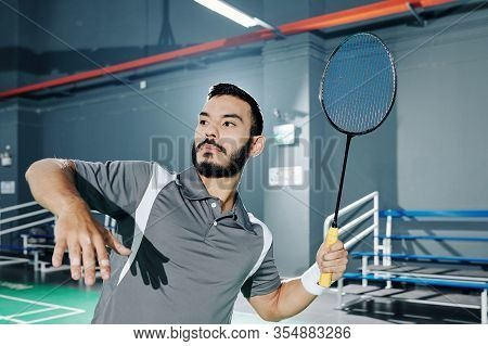 Professional Hispanic Badminton Player Hitting Shuttlecock When Playing In Gymnasium