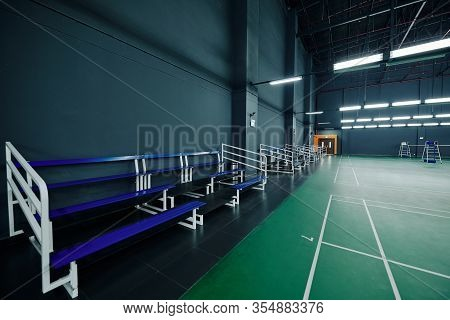 Empty Benches For Fans And Sportsmen In Gymnasium With Tennis Courts
