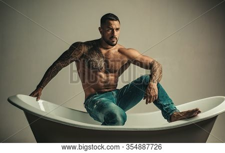 Sexual Macho Man In Bath. Strong Muscular Tattoed Man Holding Champagne Bottle And Posing In Bathroo