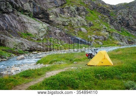 Trollstigen, Norway - July 27, 2018: Yellow Camping Tent And Mountain Bicycle On River Shore, Trolls
