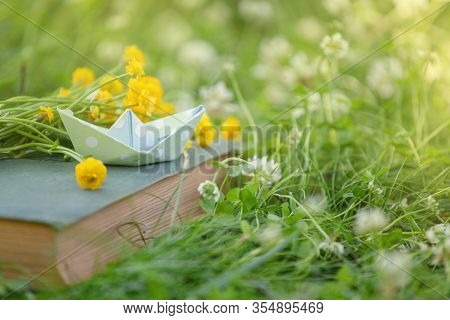 Old Book And Paper Boat Outdoor. Knowledge Is Power. Book In A Spring Summer Forest Or Garden, Yard,