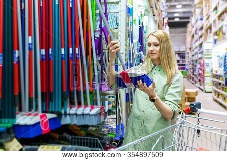 Woman Choosing Floor Cleaning Brush At Household Goods Store