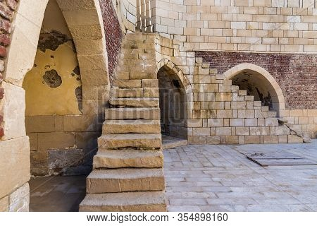 Exterior Shot Of Ancient Brick Building With Two Perpendicular Shabby Stone Stairways And Two Crumbl