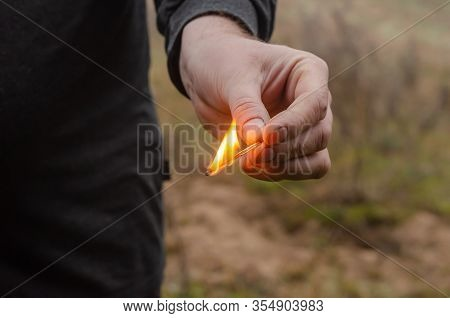 A Lit Match In A Male Hand Outdoors. A Lit Match In A Male Hand Outdoors. Adult Man Holds A Burning