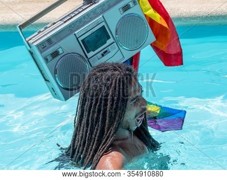 Stock Photo Of A Black Boy With Dreadlocks In The Pool With A Cassette On His Shoulder And Smiling A
