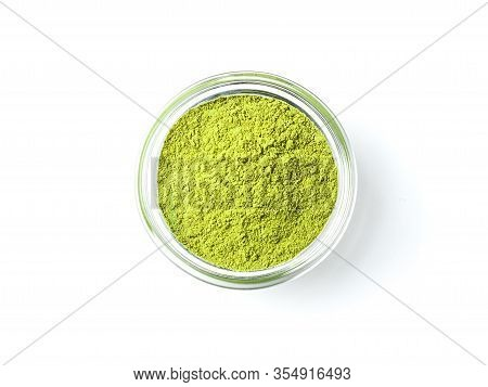 Green Matcha Tea Powder In Small Glass Bowl On White Background. Powdered Maccha Tea, Isolated On Wh