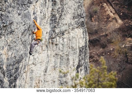 Athletic Man Climbs Very High Limestone Rock With Rope, Lead Climbing. Sport Climbing Outdoor.