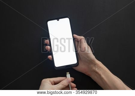 A Black Smartphone With A White Display And A Teardrop-shaped Cutout Lies On A Dark Isolated Backgro
