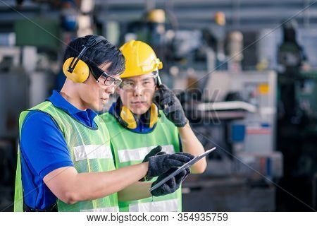Two Asian Maintenance Engineers Discuss Inspect Relay Checking Information And Protection System On