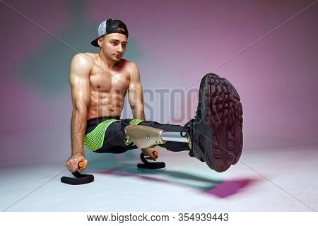 A Young Muscular Man With A Disability With A Prosthetic Leg Is Training In A Gym. Motivation Workou