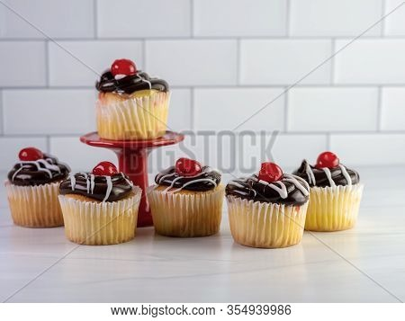6 Yellow Cupcakes Filled With Custard With Chocolate Frosting And White Drizzle With A Cherry On Top