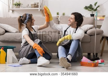 Housekeeping And Cleaning Service Concept. Happy Couple Giving High Five To Each Other After Spring-
