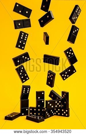 Black Dominoes Flying On Yellow Background, Closeup Scattered Dominoes On A Yellow Board Game, Game